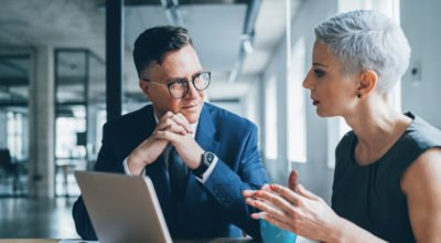 E-leadership: homem e mulher conversando no trabalho olhando para um computador