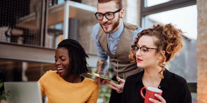 Três colegas de trabalho olhando uma tela e discutindo sobre influência social