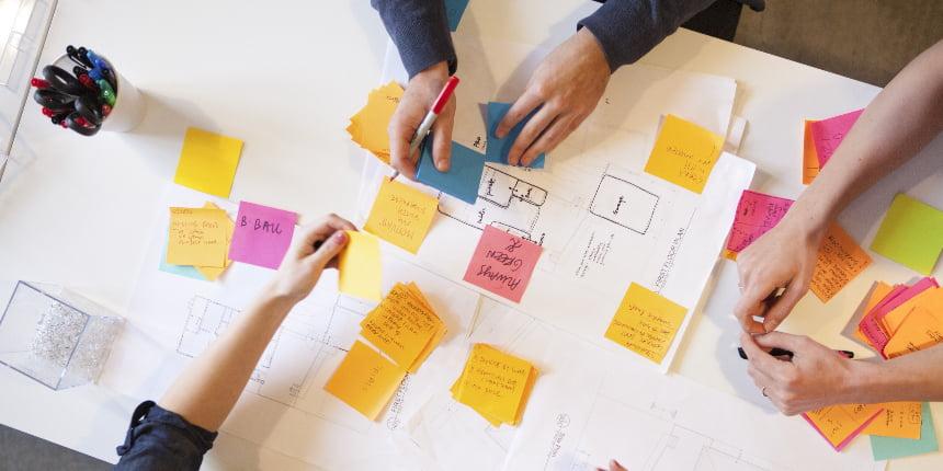 Job to Be Done: quadro com vários post-its e três colegas trabalhando nele