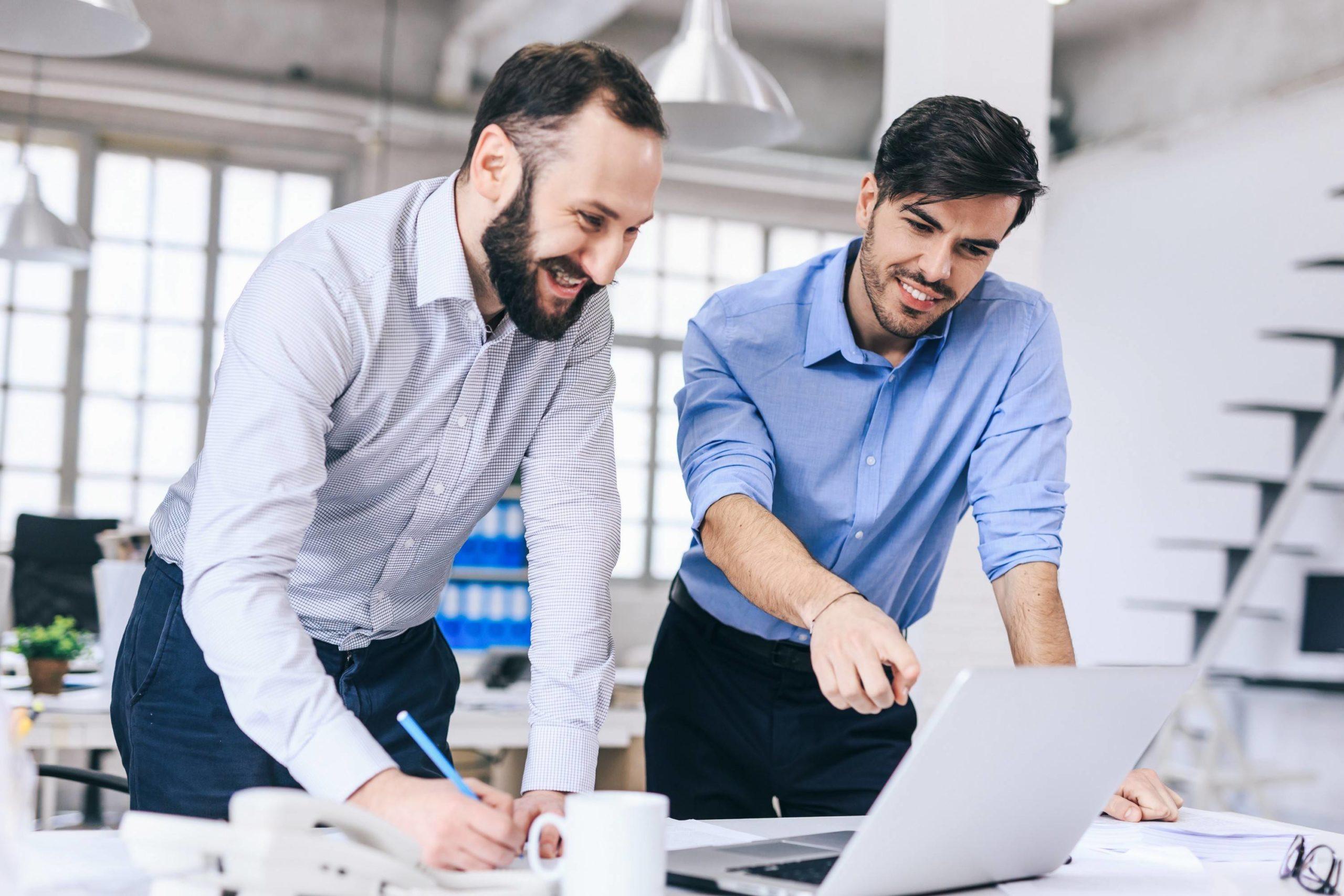 Passagem de bastão: dois homens de pé apontando para um computador em uma mesa de escritório.
