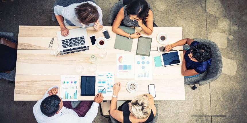 Produtividade na indústria: Mesa com 5 colegas de trabalho usando dispositivos eletrônicos.