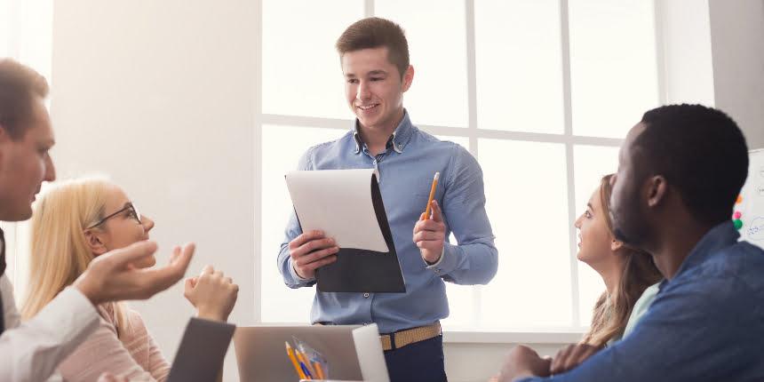 Treinamento on the job: homem fazendo uma apresentação para quatro colegas de trabalho